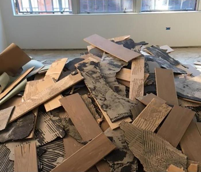 Pile of damaged floor boards removed during water damage mitigation