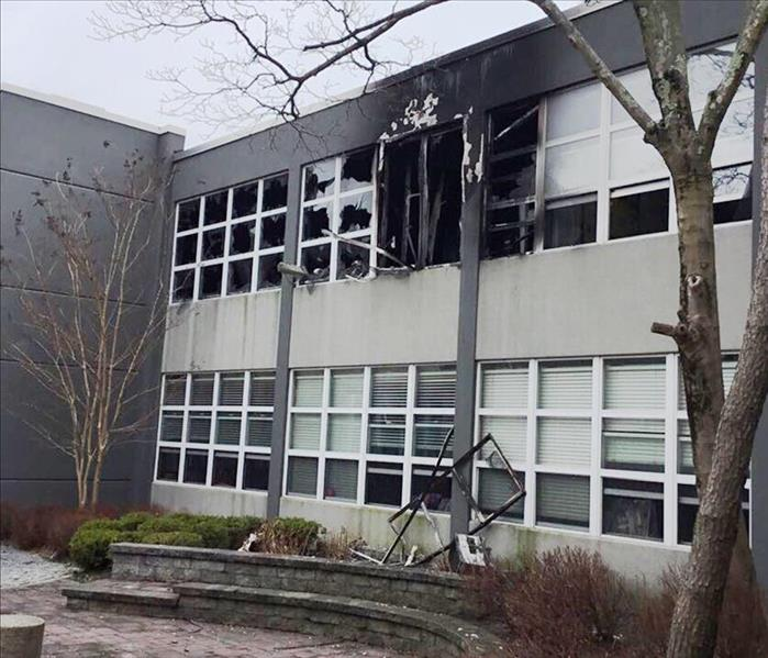 Local school exterior with broken windows and black soot from fire property damage