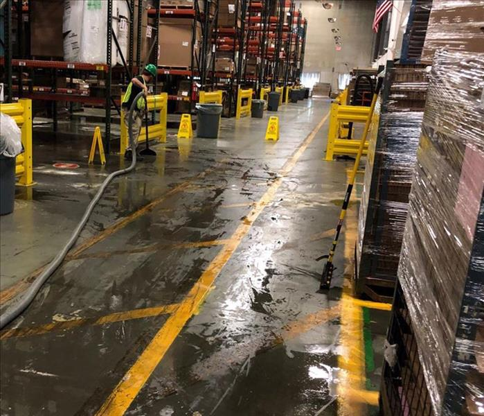 SERVPRO employee extracting water from flooded commercial warehouse floor